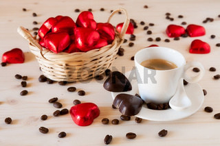Red chocolate hearts in a small basket and an espresso coffee