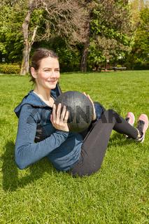 Frau trainiert mit Fitnessball auf Wiese
