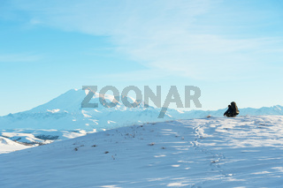 A traveler with a large backpack on his shoulders sits on a snow-capped hill against the blue sky and the sleeping Elbrus volcano surrounded by the main Caucasian ridge and meditates.