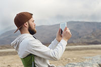 Hipster with a beard in a cap and a sweatshirt with a tablet in his hands takes pictures on a tablet while being on the nature by the lake