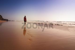 Solitary girl walking on beach