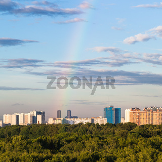 rainbow in blue sky over modern houses