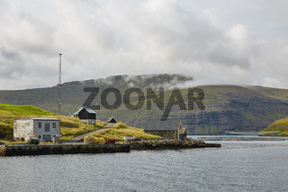 Village in wild and beautiful coastal landscape of Faroe Islands, Denmark