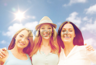 group of happy smiling women or friends over sky