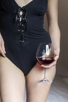 Nahaufnahme einer Frau in Unterwäsche mit Rotwein