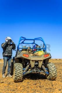 Ait Saoun, Morocco - February 23, 2016: Man preparing to ride a quad bike along the sandy desert