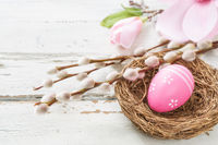 Easter nest on a rustic background with a magnolia