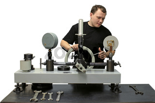 The technician works on the press. Check pressure gauge.