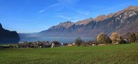 Autumn scene in Brienz. Green meadow, houses and lake Brienzersee. Mount Augstmatthorn. Landscape in Switzerland.