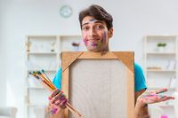 Young funny artist working on new painting in his studio