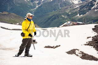 A mountaineer in a cap with glasses and an ice pick stands on a background of a snow-capped mountain