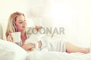 happy woman with coffee and cat in bed at home