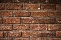 Textured background of antique decorative brick with easy vignetting. Medieval background for a brick wall