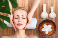 Young woman having head and face massage in spa