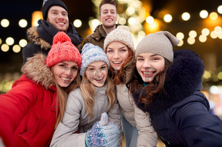happy friends taking selfie outdoors at christmas