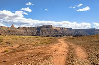 Canyon vies in Moab, Utah seen from the view of off-roading vehicles, trails and puffy white clouds