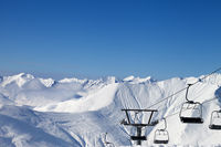 Chair lift and snowy mountains at sun cold evening