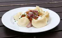 Dumplings with sour cream, bacon and onion