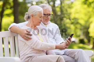 happy senior couple with smartphone at park