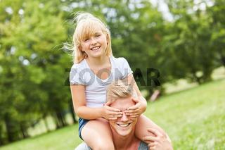 Blondes Mädchen hält Vater die Augen zu