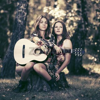 Two fashion girls with guitar in a summer forest