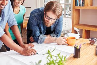 Mann und Team beim Brainstorming