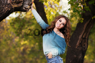 Happy young fashion woman with long curly hairs walking in city park