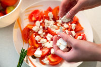 Making of tomato salad with feta cheese.