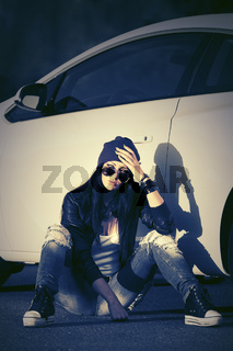 Sad young fashion woman in sunglasses sitting next to her car