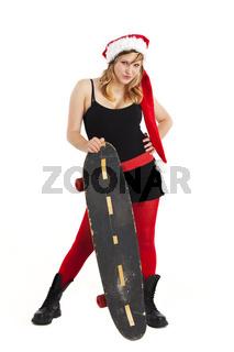 Frau mit Weihnachtsmannsmütze und einem Skateboard isoliert auf Weiß