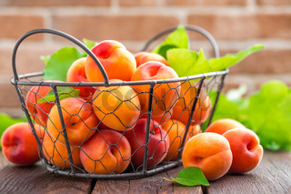 Fresh apricots with leaves in basket on wooden table