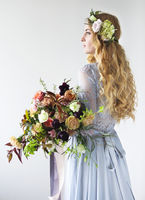 Spring beauty portrait of a bride with a wreath and a bouquet in hands