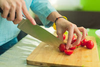 Hands of a young girl chop the cherry tomatoes on a wooden cutting board on a green table in a home setting