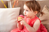 happy baby girl eating cupcake on birthday party