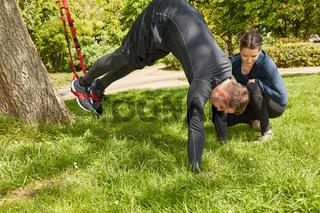 Mann bei Schlingentraining mit Personal Trainer