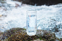 A transparent glass glass with drinking mountain water stands in the moss stone on sun beame against a background of a clean frost mountain river. The concept of drinking mountain drinking mineral water and the production of mineral environmentally friend