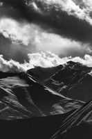 Black and white evening snowy mountains in mist