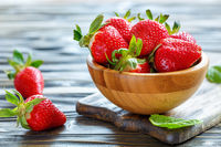 Ripe red strawberries in a wooden bowl.