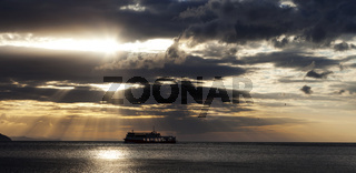 Sea with sea boat and gray sky with sun at sunset