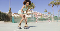 Young pretty woman riding in roller skates