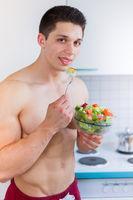 Junger Mann isst essen Salat in der Küche gesunde Ernährung Hochformat vegan