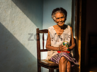 Old Cuban woman on chair enjoying a beer