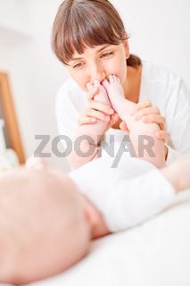 Mutter küsst liebevoll die Füße ihres Babys