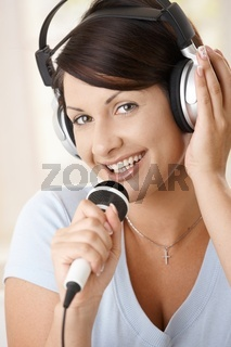 Happy woman singing at home