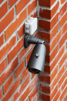 A video camera on a red brick wall protects the territory from the invasion of strangers.