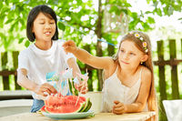 Mädchen stecken Fähnchen auf Wassermelonen