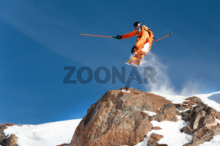 A professional skier makes a jump-drop from a high cliff against a blue sky leaving a trail of snow powder in the mountains