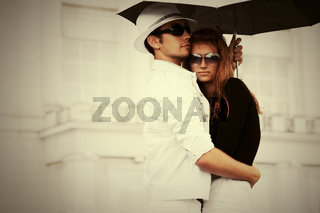 Young fashion couple in love with umbrella