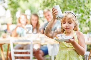 Mädchen schüttet Zucker auf ihren Kuchen