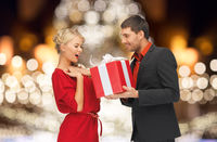 happy couple with gift over christmas tree lights